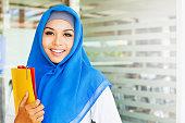 Muslim women holding her workbooks