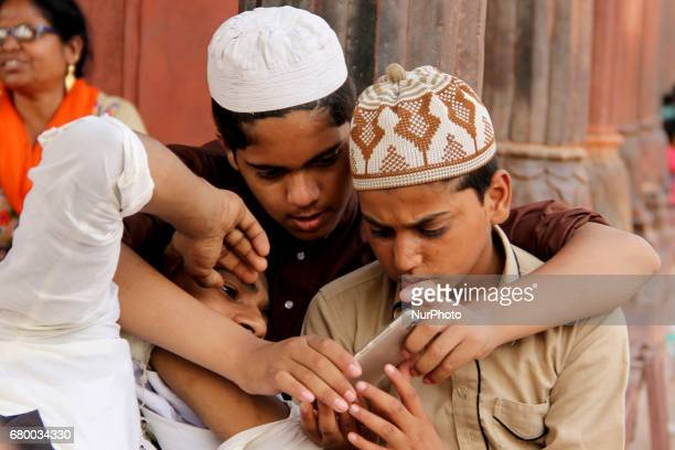 Muslim Boys checking Pictures After Photo session under sweltering sun boys are watching their clicked photographs under a shade of minarat at...