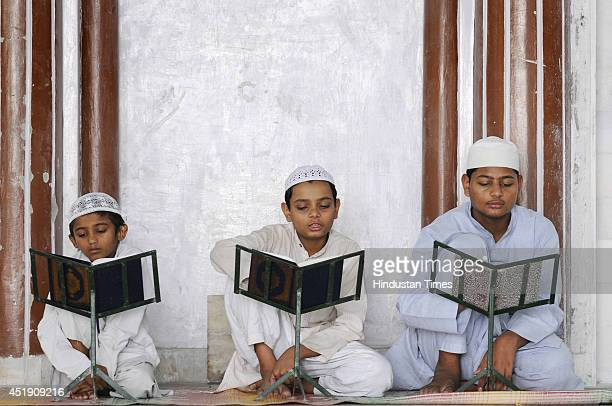Muslim boys reciting verses from Holy Book during a Quran class on the 10th day of Ramadan at a Mosque on July 9 2014 in Noida India Muslims...