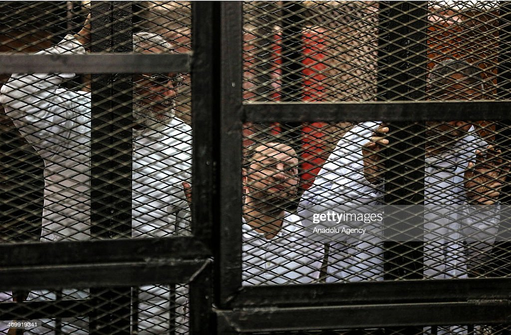 Muslim Brotherhood Leader Mohamed Badie (L) and former Minister of Supply Bassem Ouda (C) stand behind bars during the trial of Brotherhood members at a courtroom on February 17, 2014 in Cairo, Egypt. A Cairo court on Monday adjourned to February 20 the trial of Muslim Brotherhood Supreme Guide Mohamed Badie and 47 other defendants charged with inciting violence in Egypt's Qalioubiya province last summer, judicial sources said.
