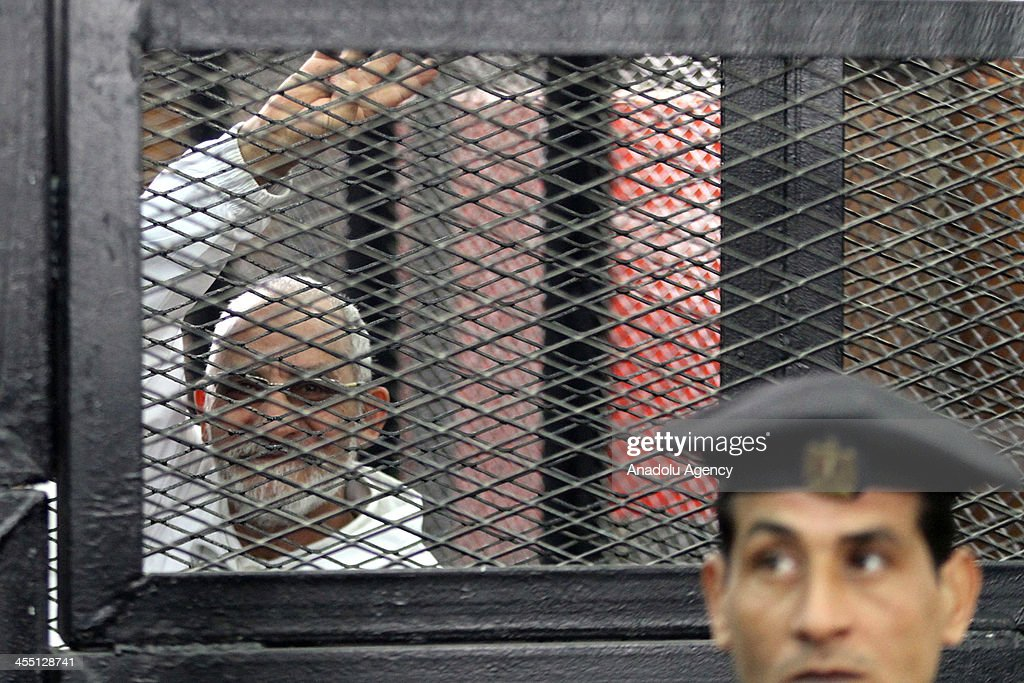 Muslim Brotherhood Leader Mohamed Badie flashes Rabaa sign behind bars during the trial of Brotherhood members at a courtroom on December 11, 2013 in Cairo, Egypt. For the second time, judges presiding over the trial of Muslim Brotherhood leader Mohamed Badie and 18 other defendants withdrew from trial proceedings on Wednesday. The defendants are accused of inciting the murder of anti-Brotherhood protesters during June 30 clashes between supporters and opponents of ousted president Morsi outside the Brotherhood's Cairo headquarters.