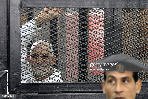 Muslim Brotherhood Leader Mohamed Badie flashes Rabaa sign behind bars during the trial of Brotherhood members at a courtroom on December 11 2013 in...