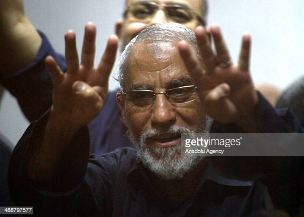 Muslim Brotherhood Leader Mohamed Badie flashes Rabia sign as he stands inside a defendant's cage during his trial at an eastern Cairo police academy...