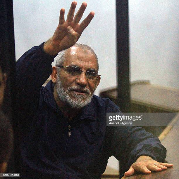 Muslim Brotherhood Leader Mohamed Badie flashes Rabia sign as he sits inside a defendant's cage during his trial in the Police Academy courthouse in...