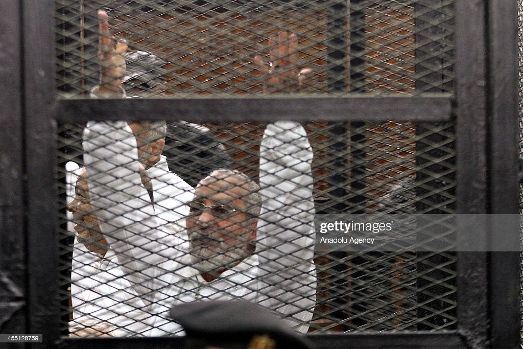 Muslim Brotherhood Leader Mohamed Badie gestures behind bars during the trial of Brotherhood members at a courtroom on December 11, 2013 in Cairo, Egypt. For the second time, judges presiding over the trial of Muslim Brotherhood leader Mohamed Badie and 18 other defendants withdrew from trial proceedings on Wednesday. The defendants are accused of inciting the murder of anti-Brotherhood protesters during June 30 clashes between supporters and opponents of ousted president Morsi outside the Brotherhood's Cairo headquarters.