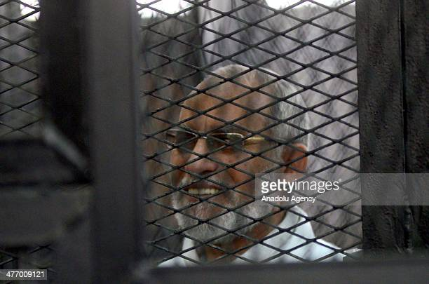 Muslim Brotherhood Leader Mohamed Badie smiles as he stands behind bars during the trial of Brotherhood members at a courtroom on March 6 2014 in...