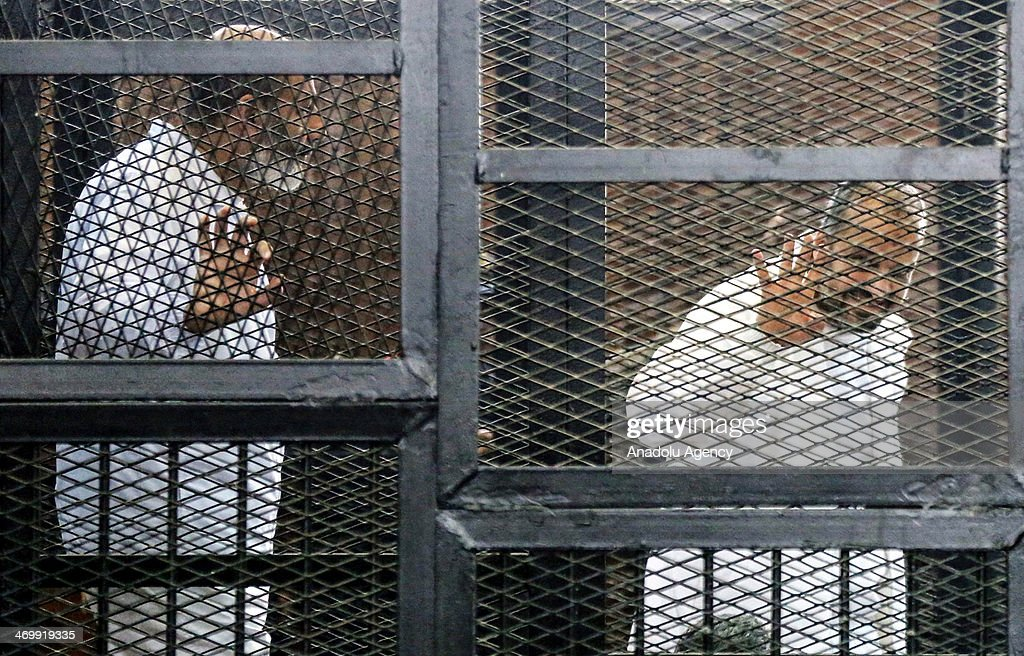 Muslim Brotherhood leaders Mohamed Beltagy (R) and Saffet Hijazi (L) stand behind bars during the trial of Brotherhood members at a courtroom in Cairo, Egypt, on February 17, 2014. A Cairo court on Monday adjourned to February 20 the trial of Muslim Brotherhood Supreme Guide Mohamed Badie and 47 other defendants charged with inciting violence in Egypt's Qalioubiya province last summer, judicial sources said.