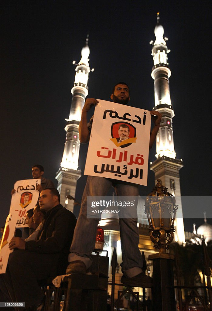 A Muslim Brotherhood member and supporter of Egyptian President Mohamed Morsi holds a banner bearing his portrait and reading in Arabic: 'support the decisions of the President' during a demonstration outside a mosque in Cairo on December 9, 2012. Egypt's main opposition parties were to meet to decide whether to keep up street protests against Morsi after the Islamist leader made a key concession in the crisis dividing the nation.