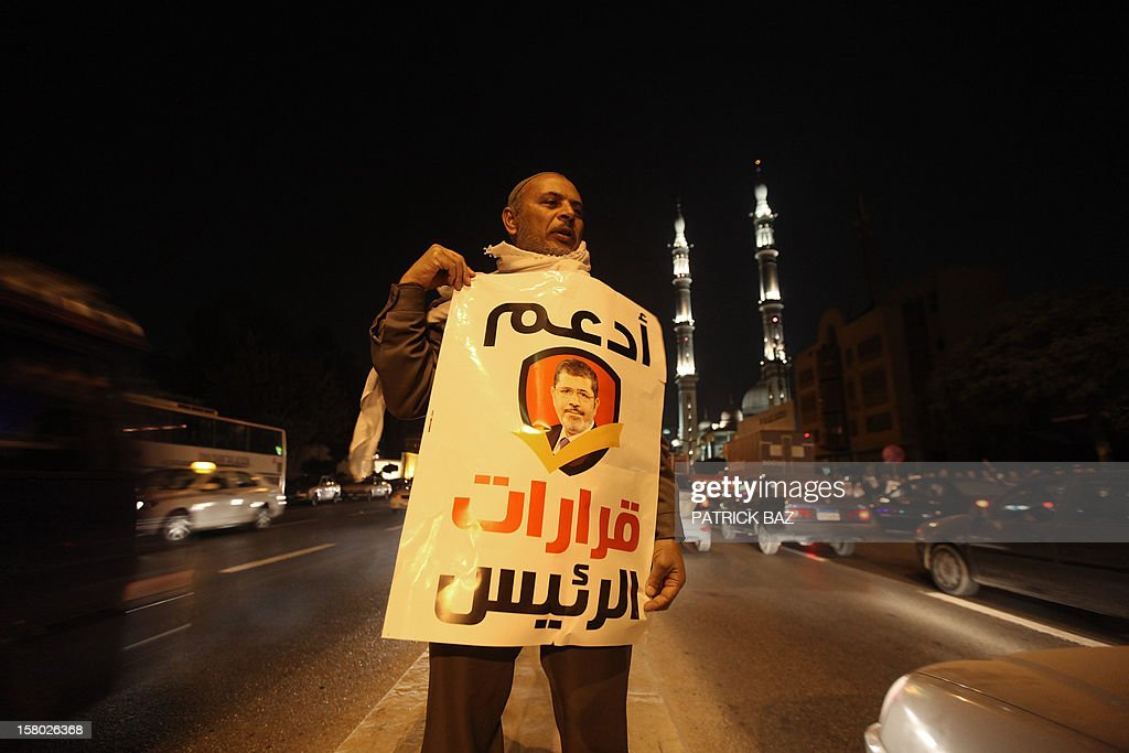 A Muslim Brotherhood member and supporter of Egyptian President Mohamed Morsi holds a banner bearing his portrait and reading in Arabic: 'support the decisions of the President' during a demonstration outside a mosque in Cairo on December 9, 2012. Egypt's main opposition parties were to meet to decide whether to keep up street protests against Morsi after the Islamist leader made a key concession in the crisis dividing the nation. AFP PHOTO/PATRICK BAZ