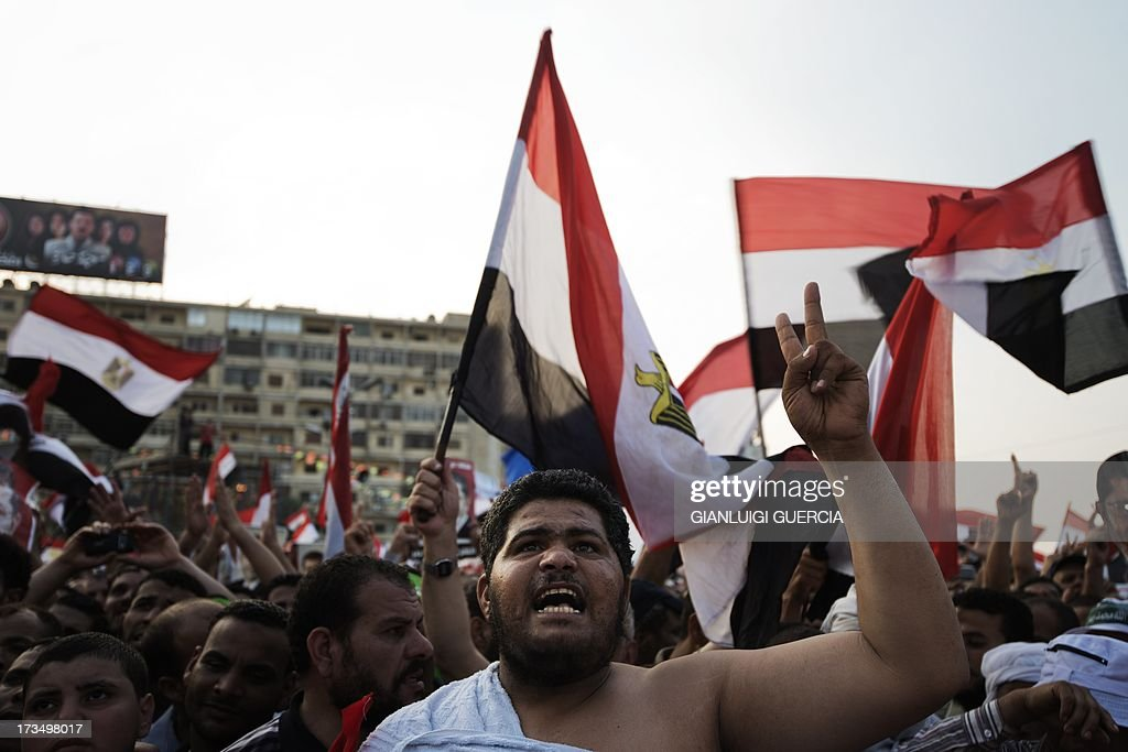 Muslim Brotherhood members and supporters of deposed president Mohamed Morsi shout slogans waving national flags during a rally outside Rabaa al-Adawiya mosque on July 15, 2013 in Cairo, Egypt. A top US official pressed Egypt's interim leaders for a return to elected government after the army ousted Morsi, whose supporters massed to rally for his return.