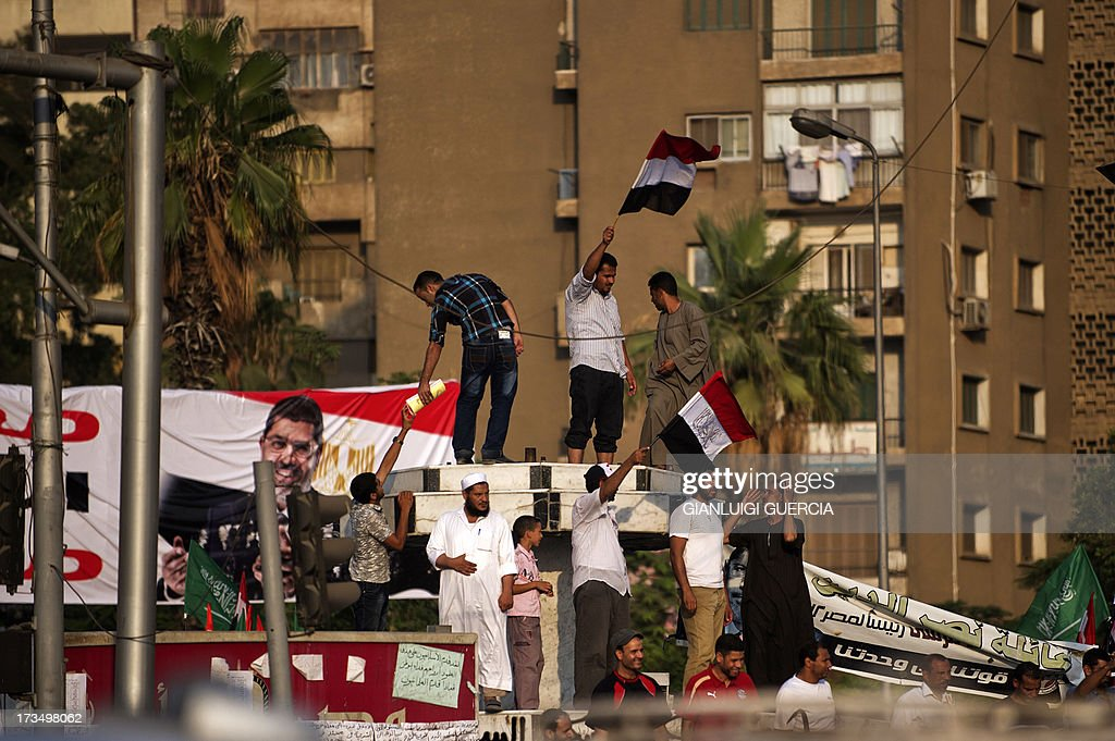 Muslim Brotherhood members and supporters of deposed president Mohamed Morsi wave national flags shouting slogans during a rally outside Rabaa al-Adawiya mosque on July 15, 2013 in Cairo, Egypt. A top US official pressed Egypt's interim leaders for a return to elected government after the army ousted Morsi, whose supporters massed to rally for his return. AFP PHOTO/GIANLUIGI GUERCIA