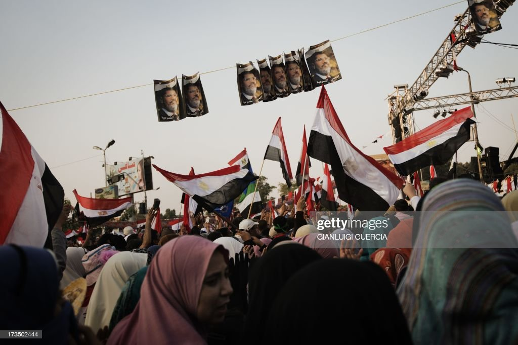 Muslim Brotherhood members and supporters of deposed president Mohamed Morsi wave national flags shouting slogans during a rally in his support outside Rabaa al-Adawiya mosque on July 15, 2013 in Cairo, Egypt. A top US official pressed Egypt's interim leaders for a return to elected government after the army ousted Morsi, whose supporters massed to rally for his return.