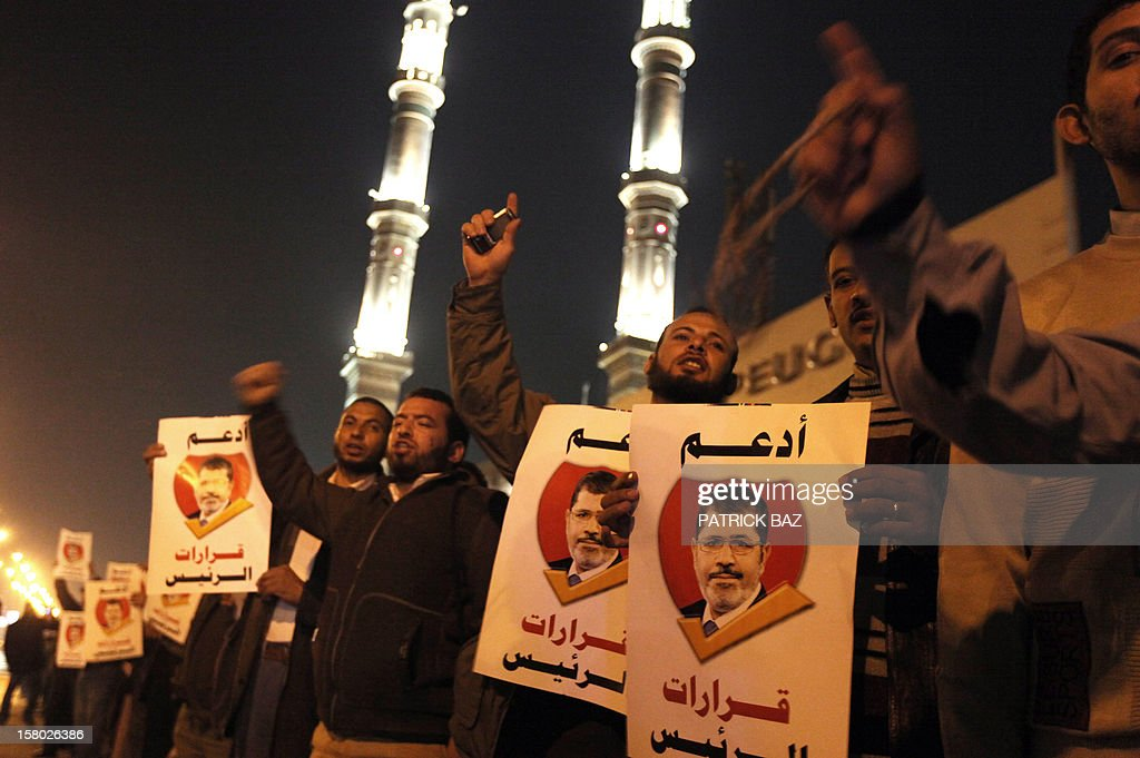 Muslim Brotherhood members and supporters of Egyptian President Mohamed Morsi shout slogans as they hold banners bearing his portrait and reading in Arabic: 'support the decisions of the President' during a demonstration outside a mosque in Cairo on December 9, 2012. Egypt's main opposition parties were to meet to decide whether to keep up street protests against Morsi after the Islamist leader made a key concession in the crisis dividing the nation. AFP PHOTO/PATRICK BAZ