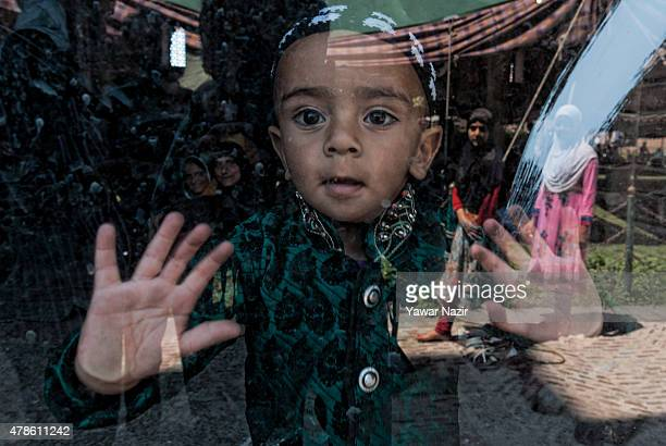 Muslim child look from the window glass as his mother offer prayers inside the Grand Mosque during the holy month of Ramadan on June 26 in Srinagar...