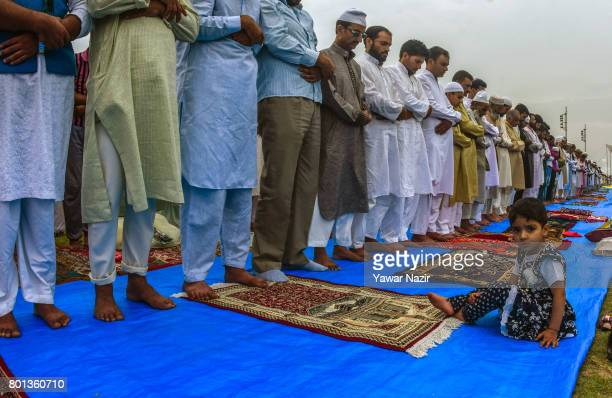 Muslim Child sits in front a row of Kashmiri Muslims offering congregational EidulFitr prayers at Eid Gah on Eidulfitr a festival of Muslims on June...