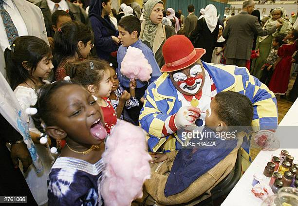 Muslim children celebrate Eid alFitr with cotton candy and face painting by a clown 25 November 2003 at the DC Armory in Washington DC Eid alFitr...