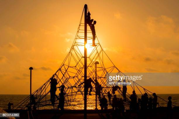 TOPSHOT Muslim children climb ropes in a park near the beach while celebrating on the second day of Eid alFitr holiday marking the end of the holy...