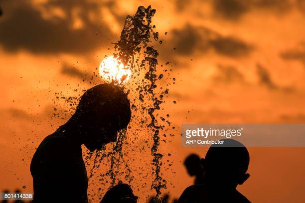 Muslim children play in a water fountain near the beach while celebrating on the second day of Eid alFitr holiday marking the end of the holy fasting...
