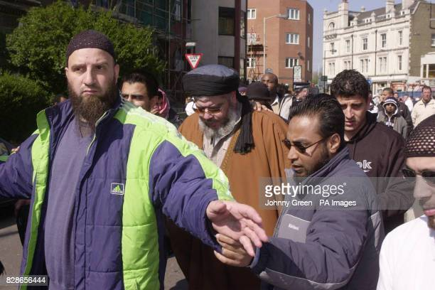 Muslim cleric Abu Hamza is lead away from the press after addressing an audience of around 120 during lunchtime prayers outside Finsbury Park Mosque...