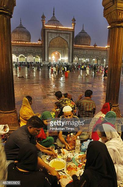 Muslim couple waits to have their Iftar meal on eve of Eid at Jama Masjid on July 28 2014 in New Delhi India Shahi Imam Mufti Mohammed Mukarram Ahmed...