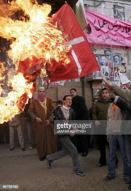 Muslim demonstrators burn a Danish flag 03 February 2006 in the West Bank town of Nablus where Muslims have been demonstrating against the countries...