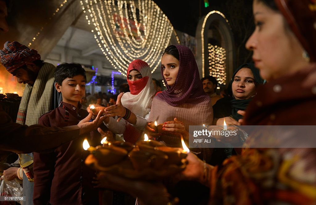 Muslim devotees light candles around a fire at the shrine of Sufi saint Hazrat Shah Hussain popularly known as Madhu Lal Hussain during annual...