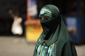 A Muslim ethnic Uighur woman walks on a street in Urumqi capital of China's Xinjiang region on July 3 2010 ahead of the first anniversary of bloody...