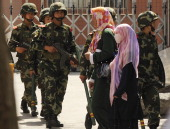 Muslim ethnic Uighur women pass a Chinese paramilatary police on patrol on a street in Urumqi capital of China's Xinjiang region on July 3 2010 ahead...