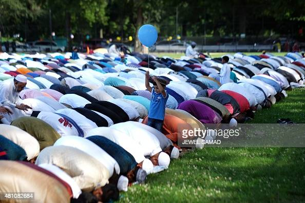 Muslim faithfuls take part in a special morning prayer to start their Eid alFitr celebrations on a field at the Prospect Park in Brooklyn borough of...