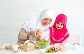 Muslim family, mother and daughter, wear hijab help to pour olive oil to vegetable salad in glass bowl with the other food on white table and both stay in front of white background.