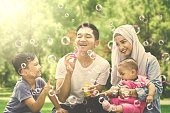 Image of Muslim family playing with soap bubble while squatting in the park