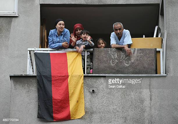 Muslim family who indiciated they did not mind being photographed look down from a balcony where a German flag is hanging for the World Cup during a...