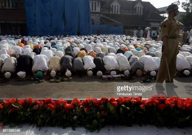 Muslim Festival EID A policeman maintains vigil as the faithful bow in prayer at the Bandra masjid on the occasion of EId Seen in the foreground is a...