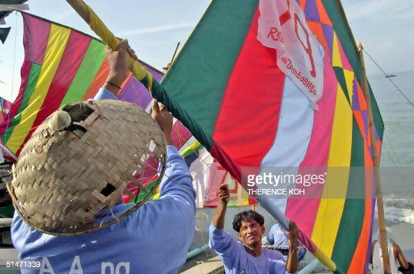 Muslim fishermen belonging to the seadwelling Samal and Badjao tribes fix colorful sails on their small fishing boat for a race 10 October 2004 as...