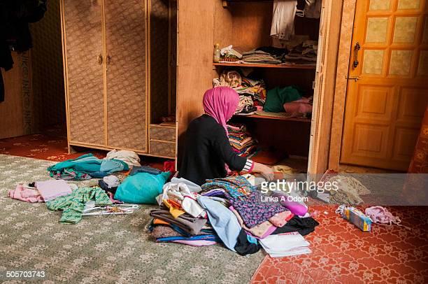 A Muslim Girl Organizing Clean Laundry