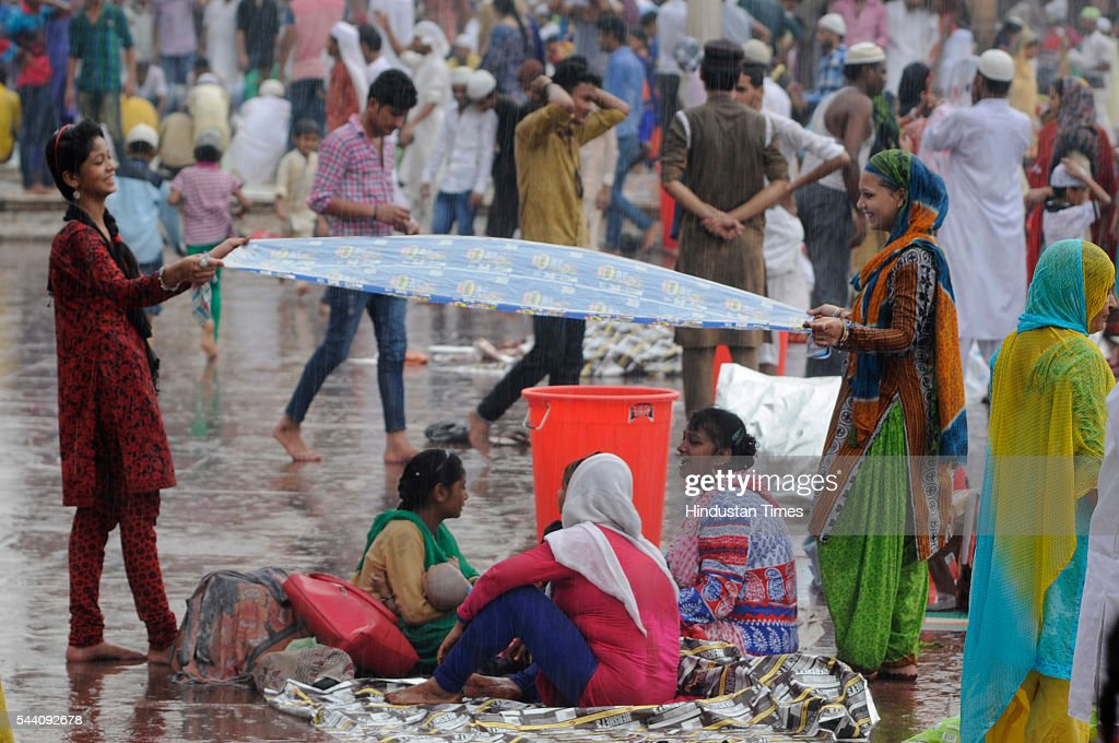 Muslim girls hold a plastic sheet to protect their family as it rain heavily near Jama Masjid on July 1, 2016 in New Delhi, India. The capital received its first Monsoon rains dragging the maximum temperatures several notches below normal. Heavy downpour caused water logging and traffic jams in the city.