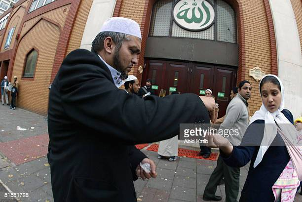 Muslim gives money to a beggar after the Friday prayer in front of the East London Mosque on the second Friday of the Muslim holy month of Ramadan...
