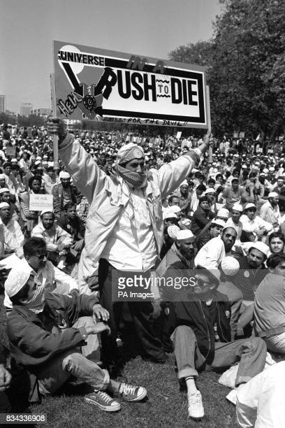 A Muslim holds aloft a dramatic banner in Hyde park during a protest against Satanic Verses author Salman Rushdie