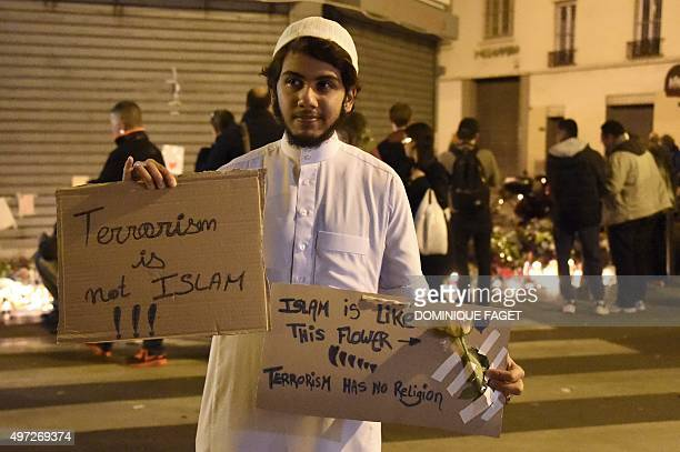 A muslim holds placard reading 'Terrorism is not Islam Islam is like this flower Terrorsim has no religion' during a gathering at 'Le Carillon'...