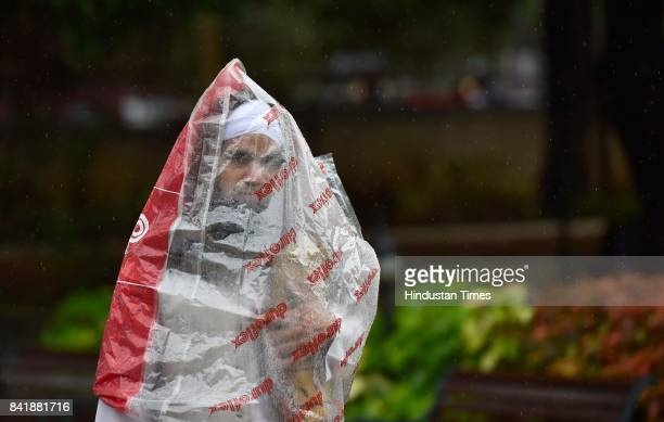 Muslim man covers himself on his way to offer prayer amid heavy rain on the occasion of Eid alAdha the festival of sacrifice at MasjideKhadira on...