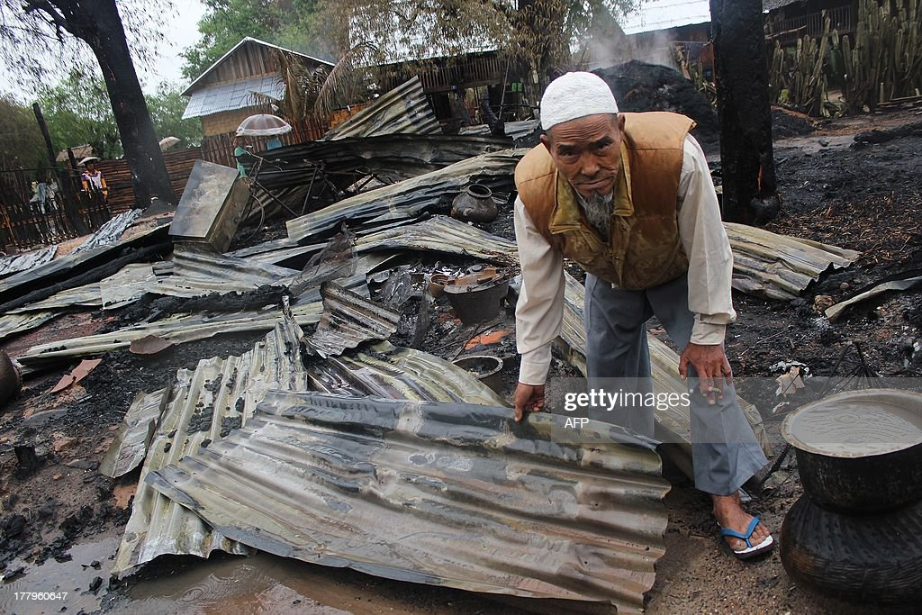 A Muslim man inspects the debris of his burned house in Htan Gone village on August 26, 2013, after some 1,000 anti-Muslim rioters rampaged through villages in Kanbalu township, in the central region of Sagaing on August 24, setting fire to property and attacking rescue vehicles. Hundreds of people made homeless by Myanmar's latest eruption of religious violence were sheltering in a school on August 26, a local MP said, after mobs torched the homes and shops of local Muslims. AFP PHOTO/Mantharlay