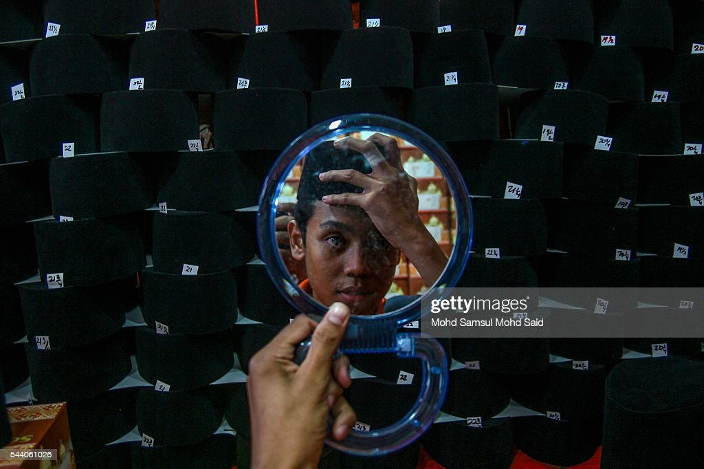 A Muslim man is seen on mirror when he try a size of Malay traditional songkok ahead of the Eid al-Fitri festival on July 1, 2016 in Kuala Lumpur, Malaysia. Southeast Asia's Muslims are observing the fasting month of Ramadan, Islam's holiest month, during which observant believers fast from dawn to dusk. Malaysia Muslims spend extra on food and new clothes for Eid al-Fitr, the most important festival in Islam, which marks the end of Ramadan spending seems to be holding up in Malaysia and in neighbouring Indonesia, which together account for about 14 percent of the world's Muslims.