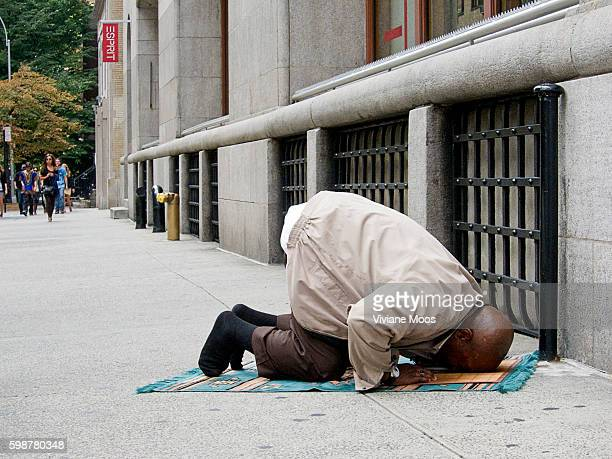A Muslim man kneels on his prayer mat praying bowing towards Mecca on the sidewalk in the middle of Manhattan