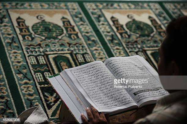 Muslim man reads the Quran as he waits for the breaking of the fast during Ramadan on July 13 2014 in Surabaya Indonesia Ramadan the ninth month of...