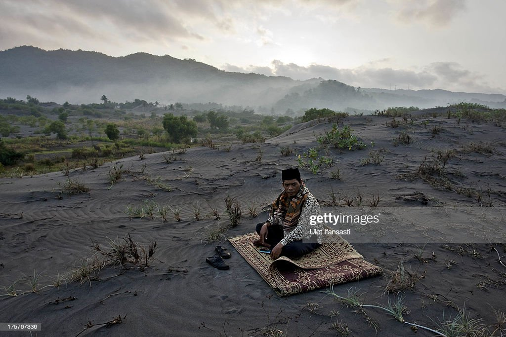 A muslim man sits on 'sea of sands' as he waits for Eid Al-Fitr prayer at Parangkusumo Beach on August 8, 2013 in Yogyakarta, Indonesia. Eid Al-Fitr, marks the end of Ramadan, the Islamic month of fasting and begins after the sighting of a new crescent moon.