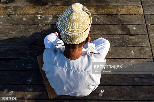 A Muslim man wearing a traditional kuma sitting on a fish market jetty.