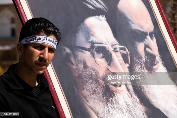Muslim man with a portrait of the ayatollah Jomeini and Khamenei