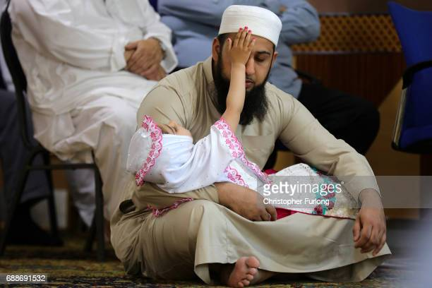 Muslim man with a young child attends Friday prayers at Manchester Central Mosque where they prayed for those who were killed or injured in the...