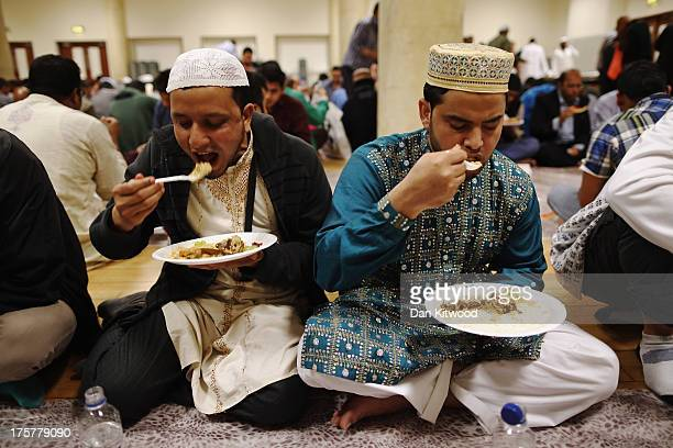 Muslim men break fast with Iftar at the East London Mosque on the last day of Ramadan on August 7 2013 in London England Iftar is the break of the...