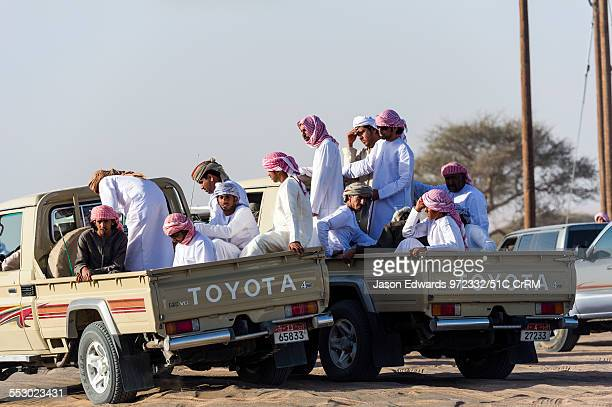 Muslim men gather in the back of 4WD vehicles to follow the camels as they race on a desert track Bidiya Sharqiya Region Sultanate of Oman